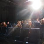 Ein Saal verdunkelt sich - der Projektionsstrahl zeigt seine Herrschaft.